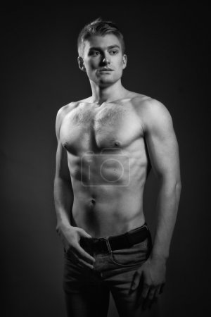 Photo for Sexual muscular man posing over dark background - Royalty Free Image