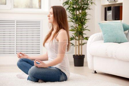 Photo pour Femme assise sur le sol à la maison faisant méditation de yoga - image libre de droit