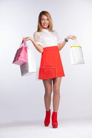 Photo pour Belle femme pleine longueur avec des sacs à provisions sur gris - image libre de droit