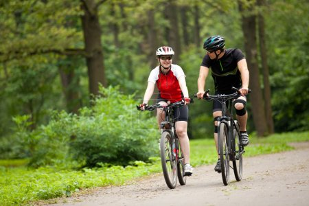 Photo for Happy Man and woman exercising with bicycles outdoors, they are a couple in park - Royalty Free Image
