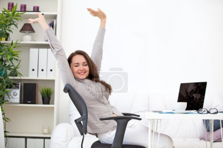 Photo for Attractive, young woman stretching at her workplace and smiling in the office - Royalty Free Image