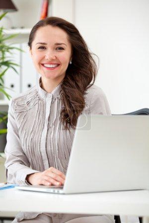 Photo pour Sourire de femme d'affaires travaillant sur ordinateur portable au bureau - image libre de droit