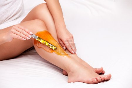 Photo pour Application de cire à jambe de femelles pour enlever les poils sur blanc - image libre de droit