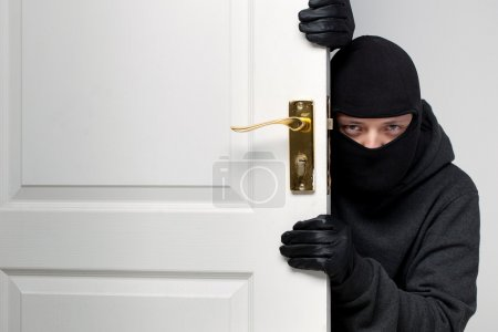 Burglar sneaking in a open house door