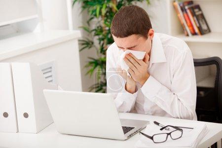 Man sneezing while working