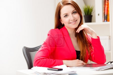 Photo for Smiling woman sitting in office - Royalty Free Image