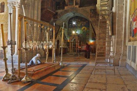 Photo pour Temple du Saint Sépulcre à Jérusalem. Le plus ancien sanctuaire chrétien - Pierre de l'Onction. Le pèlerin en vêtements blancs prie sous les lampes d'icône - image libre de droit