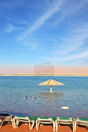 Photo pour Belle journée ensoleillée à une station balnéaire. la mer morte, des parasols et des transats pour les touristes en attente - image libre de droit