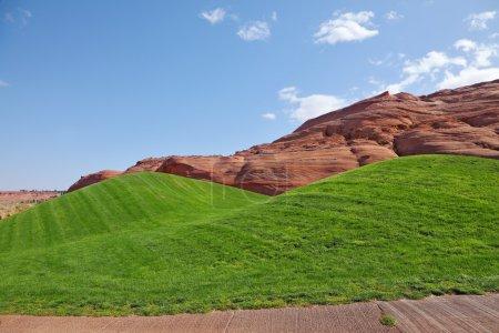 Photo pour Collines de grès rouge et vertes collines herbeuses pour un golf - image libre de droit