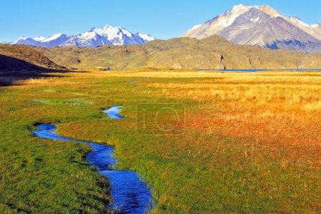 Photo pour L'immense vallée entourée de montagnes enneigées. Traverse la vallée pittoresque du ruisseau. L'Estancia solitaire dans le parc national Perito Moreno en Argentine . - image libre de droit
