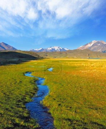 Photo pour Une Estancia solitaire dans le parc national Perito Moreno en Argentine. Une immense vallée entourée de montagnes enneigées. Traverse la vallée pittoresque du ruisseau - image libre de droit