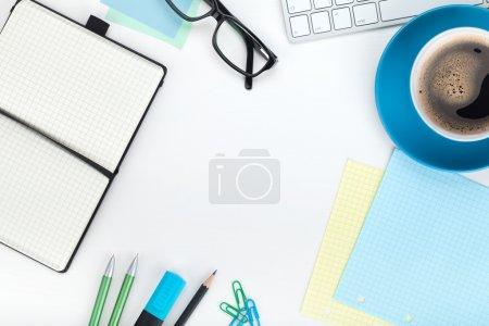Photo pour Tasse à café bleue et fournitures de bureau. Vue d'en haut. Gros plan sur fond blanc - image libre de droit