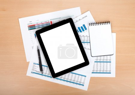 Tablet with blank screen over papers with numbers and charts