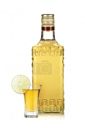 Bottle of gold tequila and shot with lime slice