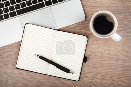 Photo for Notepad, laptop and coffee cup on wood table. View from above - Royalty Free Image