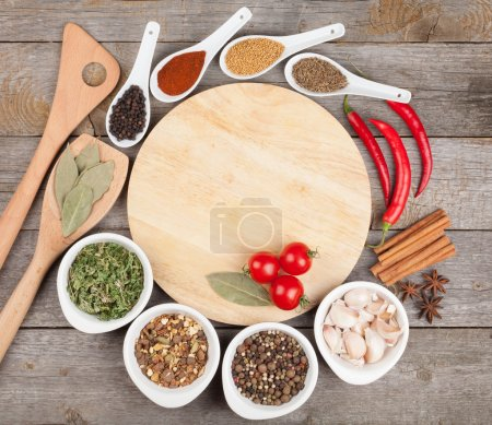 Photo for Colorful herbs and spices selection. Aromatic ingredients on wood table with empty cutting board for copyspace - Royalty Free Image