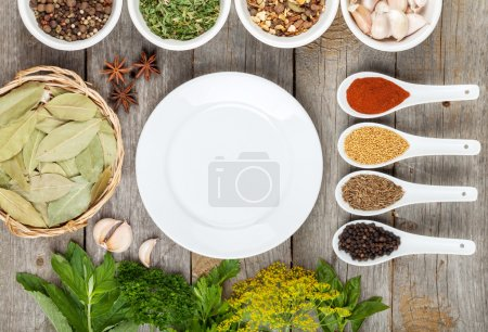 Photo for Colorful herbs and spices selection. Aromatic ingredients on wood table with empty plate for copyspace - Royalty Free Image