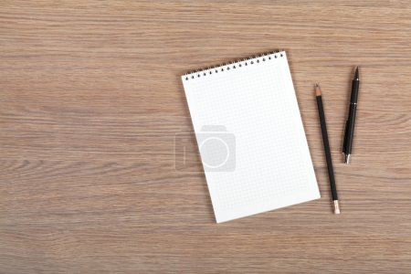 Photo for Blank notepad with pen and pencil on office wooden table - Royalty Free Image