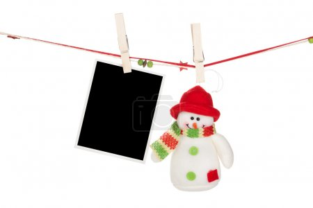 Blank photo frame and snowman hanging on the clothesline