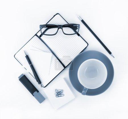 Photo pour Tasse à café et fournitures de bureau. Vue d'en haut. Bleu tonique - image libre de droit