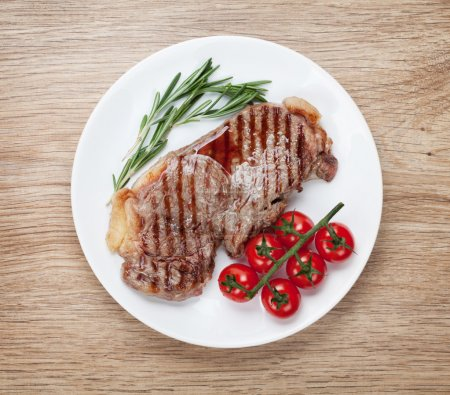 Photo for Sirloin steak with rosemary and cherry tomatoes on a plate. View from above - Royalty Free Image