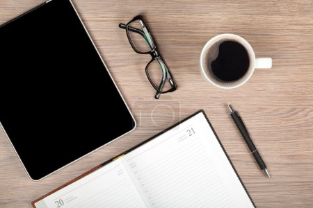 Photo for Tablet, notepad, glasses and coffee cup on office wooden table - Royalty Free Image