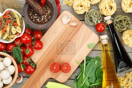 Photo for Fresh ingredients for cooking: pasta, tomato and spices over wooden table background with copy space - Royalty Free Image