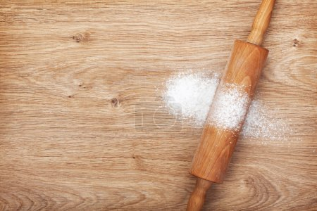 Photo for Rolling pin with flour on wooden table. View from above - Royalty Free Image