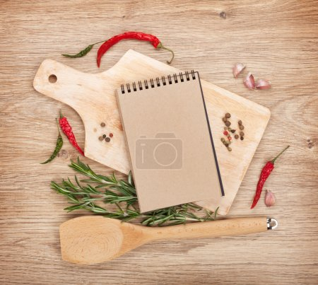 Photo for Blank notepad on cutting board with spices around over wooden table - Royalty Free Image