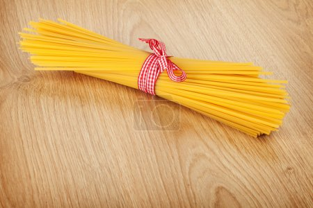 Photo for Bunch of spaghetti on wooden table background - Royalty Free Image