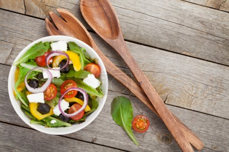 Photo for Fresh healty salad on wooden table and kitchen utensil. View from above - Royalty Free Image