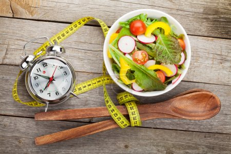 Photo for Fresh healthy salad and measuring tape on wooden table. Healthy food - Royalty Free Image