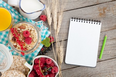 Photo for Healty breakfast with muesli, berries and orange juice. View from above on wooden table with notepad for copy space - Royalty Free Image