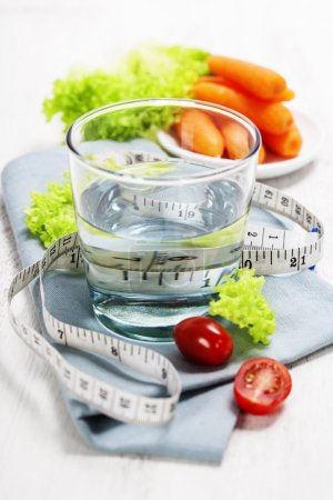 Photo for Fresh vegetables and measurement tape - diet and healthy eating concept - over white - Royalty Free Image
