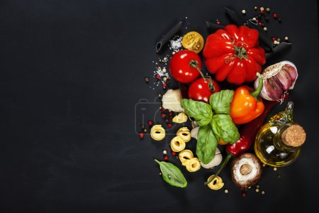 Photo for Italian ingredients - pasta, vegetables, spices, cheese - on dark background - Royalty Free Image