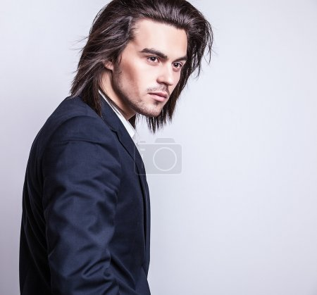 Elegant young handsome long-haired man in costume. Studio fashion portrait.