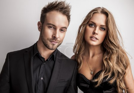 Photo pour Portrait de jeune couple attrayant posant en studio habillé de vêtements noirs à la mode . - image libre de droit