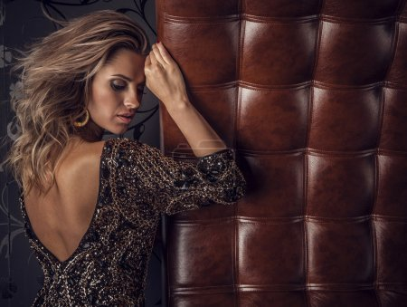 Young sensual & beauty woman posing on luxury leather sofa.