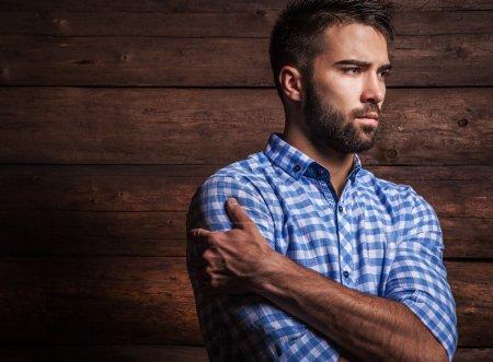 Photo pour Portrait de jeune bel homme à la mode contre un mur en bois . - image libre de droit