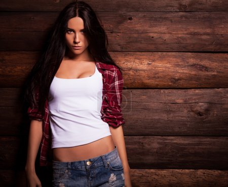 Young sensual & beauty woman in casual clothes pose on grunge wooden background.