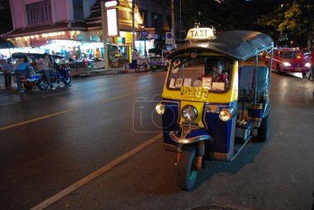 Bangkok: A three wheeled tuk tuk taxi on a street