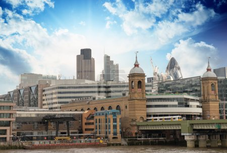 City of London with clouds, financial center and Canary Wharf at