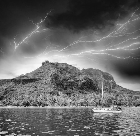 Polynesia. Island and vegetation during a storm with small boat