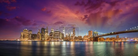 Photo for New York City Manhattan skyline panorama with Brooklyn Bridge and office skyscrapers buildings at dusk illuminated with lights at night. - Royalty Free Image