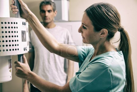Young female doctor checking x-ray machine before a male patient