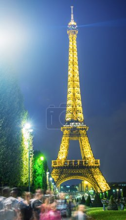 Eiffel Tower night lights with trees.