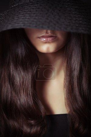 Photo pour Jeune belle femme aux cheveux longs dans l'obscurité, plan studio - image libre de droit