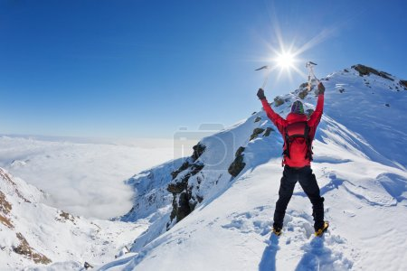 Photo for Mountaineer reaches the top of a snowy mountain in a sunny winter day. - Royalty Free Image