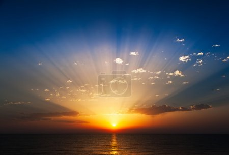 Photo for Perfect sunrise on the sea, with radiant rays of sun over a warm colourful horizont. - Royalty Free Image