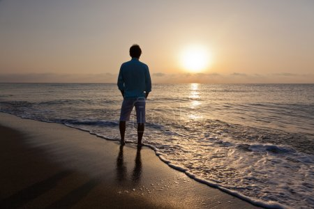Man alone on beach watching the sunset
